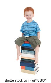 Young boy sitting on stack of books. Isolated on white.