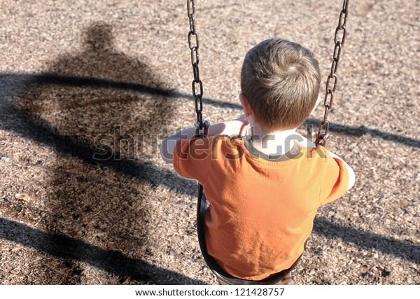Un niño está sentado en un columpio y mirando a la sombra de un hombre o matón en un patio de recreo. Utilícelo para un concepto de secuestro, defensa o seguridad.