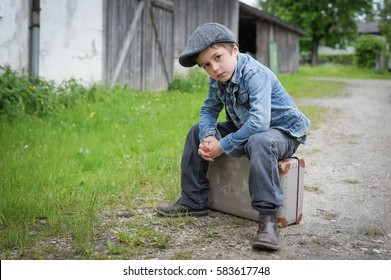 Young boy sitting on vintage suitcase waiting outdoor to run away from home to travel the world