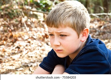 A young boy sitting outdoors, maybe he's thinking, not feeling well, or lost, the expression could relate to many emotions.