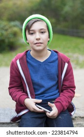 young boy sitting outside and holding a phone