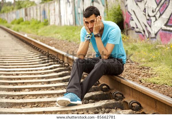 Young boy sitting at railway.