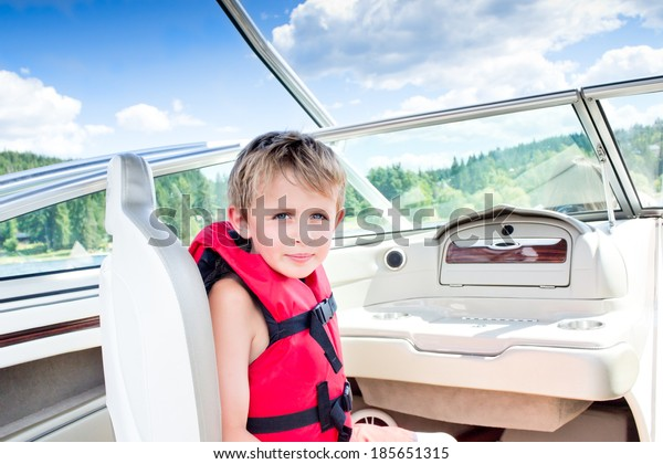 Young Boy sitting in the seat of a speedboat in summer