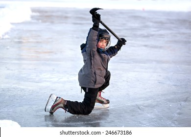 Young boy skating and playing pond hockey outdoors