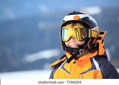 A young boy skier in his snow gear.