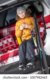Young boy skier sitting in car boot and drinking tea from mug. Winter