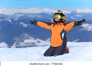 Young boy skier sitting in snow with arms stretched out.