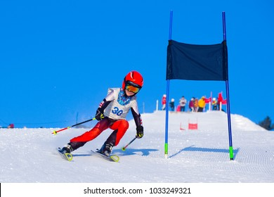 Young boy skiing in mountains. Active  kid with safety helmet, goggles and poles. Ski race for young children