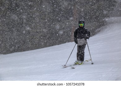 young boy skiing in a snow storm