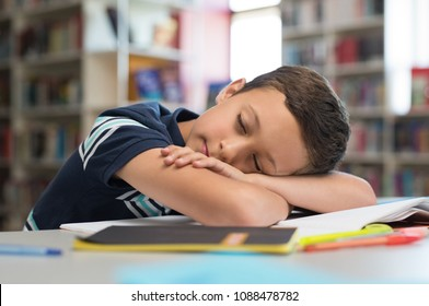 Young boy sleeps on library desk. Tired pupil fell asleep while studying on table with books. Cute child lying on books and sleeping in class during lesson. Sleepy schoolboy at school.