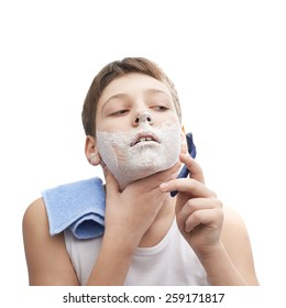 Young boy in a sleeveless white shirt with his face covered with the shaving foam, in process of shaving, composition isolated over the white background