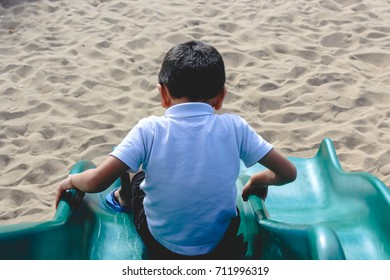 A young boy sliding down a playground slide