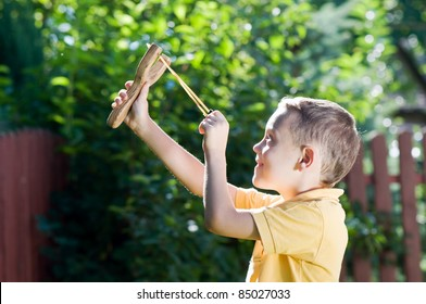 young boy with slingshot shooting