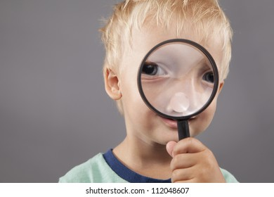 A young boy smiles and holds a magnifying glass up to his face.