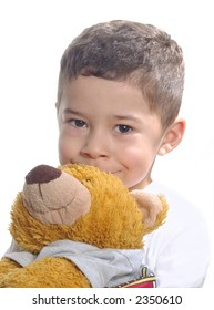 A young boy smiling behind his teddy bear
