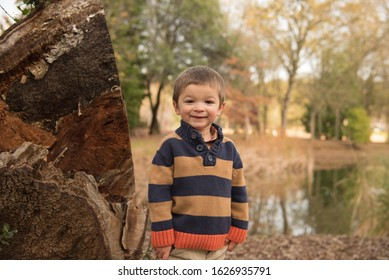 Young boy smiling in fall colors near lake