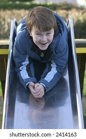 A young boy smiling as he goes down a steel slide in the park