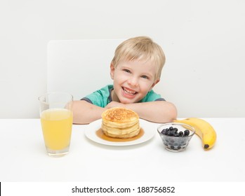 A young boy smiling with his breakfast of pancakes, berries, banana and juice taken against a white background.