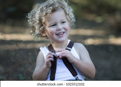 A young boy is smiling and looks very happy. He has blonde curly hair. The child is wearing a white tank top with brown suspenders, which is in between his fingers. Happy portrait of a little boy.