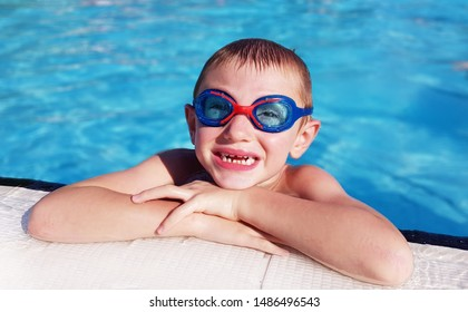 young boy is smiling in the water of swimmingpool