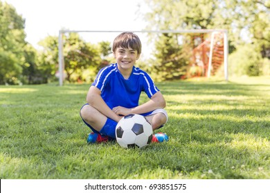 A Young boy with soccer ball on a sport uniform