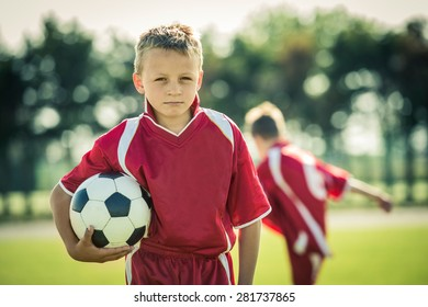 Young boy with soccer ball posing for picture