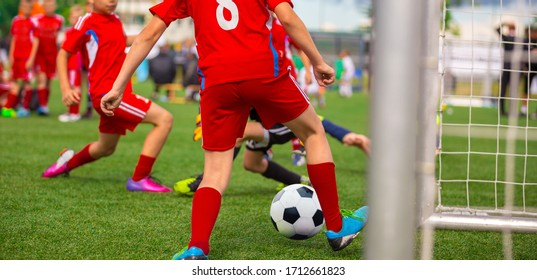 Young Boy Soccer Player Scoring Goal in Match. Junior Level School Footballers Kicking Soccer Tournament Game. Boys Score Soccer Goal. Competition Between Striker and Goalie. Youth Soccer Background