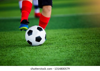 young boy soccer players run to trap and control the ball for shoot to goal. Soccer players fighting each other by kicking the ball