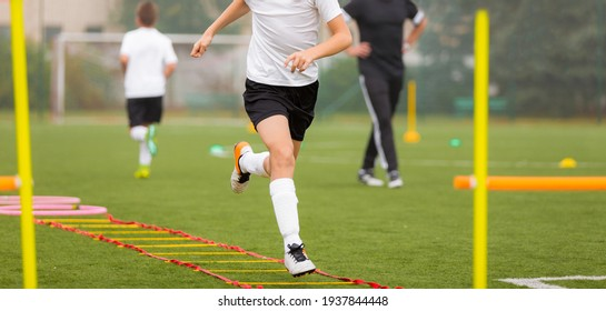 Young boy in soccer shoes cleats running through training ladder. Coach in the background. Football agility training for youth soccer club