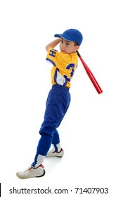 A young boy in a softball, baseball or t-ball uniform swings a bat.  White background.