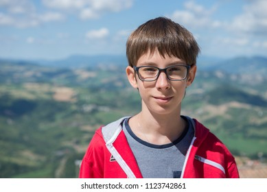 Young boy spectacled looking at camera outdoor over San Marino city-state. Vision, eyesight, sight, diopters, spectacles, glasses, health.