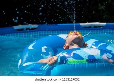 young boy spitting water upward in backyard pool