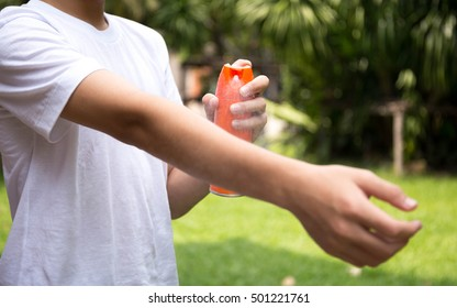 Young boy spraying insect repellents on skin in the garden with spray bottle