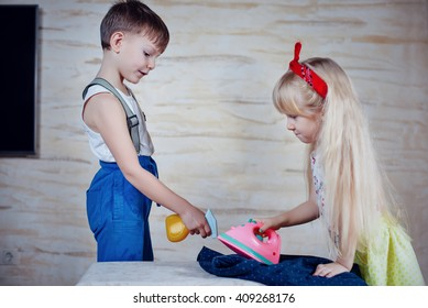Young boy spraying the laundry as it is being ironed by a pretty little blond girl playing housewife using a pink plastic toy iron