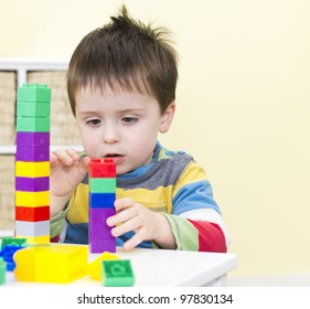Young boy stacks connecting blocks