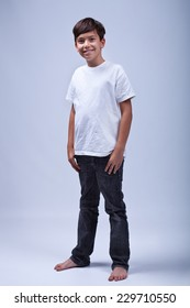Young boy standing barefoot wearing casual clothes