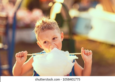 Young boy standing and biting candy cotton on the street in sunny day.