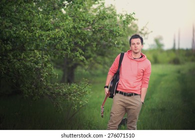 A young boy standing with his guitar on the background of nature