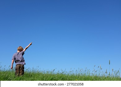 Young boy standing in meadow pointing to sky