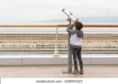A young boy standing on his toes, exploring the sky with a telescope