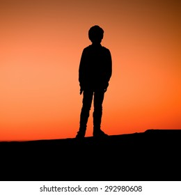 A young boy is standing on a pier enjoying the red sunset. Silhouette of a kid