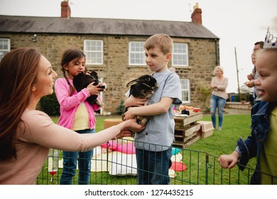 Young boy standing outdoors, a mid adult woman is handing him a bubby rabbit to hold.