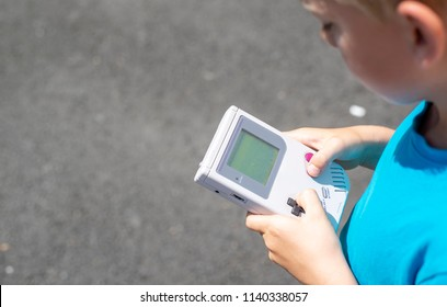 Young boy standing outside playing his video game.