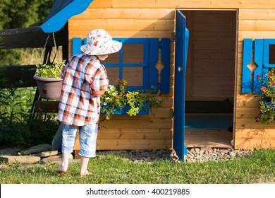 young boy standing and playing outside the children wooden playhouse with blue windows and blooming flowers in the countryside garden