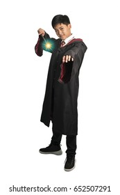 Young boy stands with magic wand casting spells on a white background