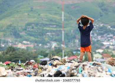 The young boy stands to the top of a garbage heap. I took this photo in Philippines.