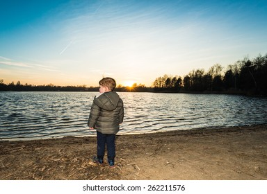 young boy staring over the water at sunset