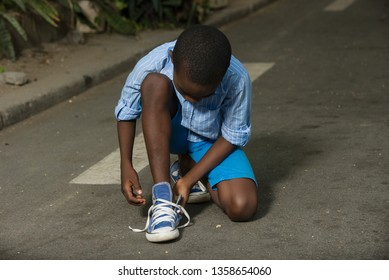 young boy in striped shirt squatting in the street adjusting his lace.