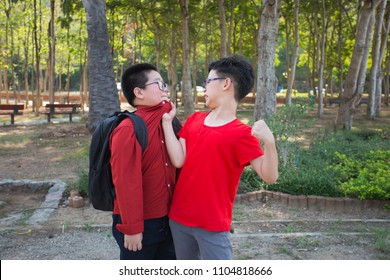Young boy students fighting  in the park