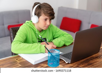 Young boy is studying in front of the laptop. E learning, study at home online. - Shutterstock ID 1690371118